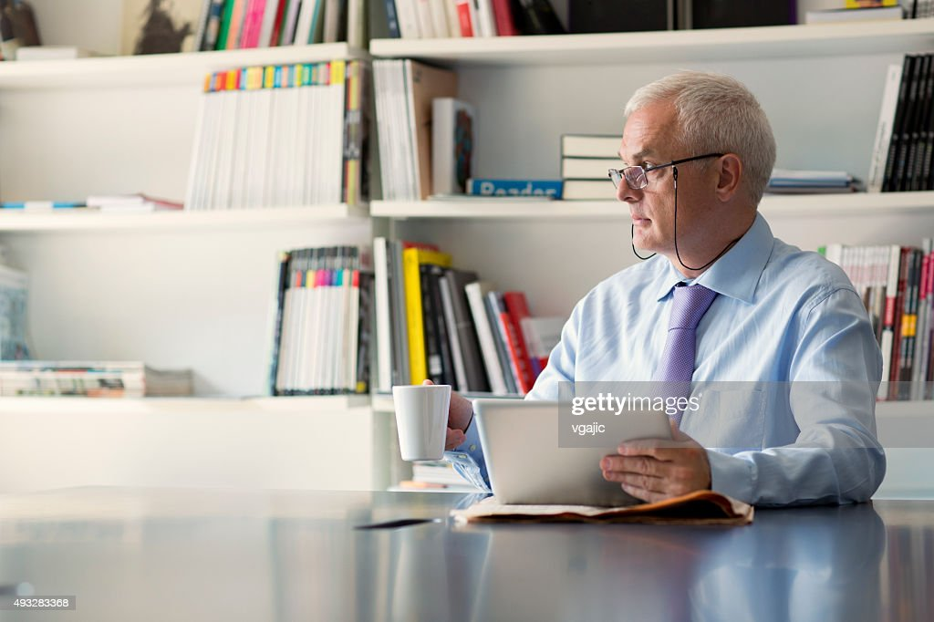 Senior businessman using digital tablet in office.