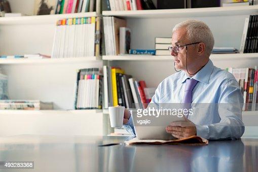Senior businessman using digital tablet in office.