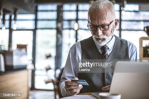Senior businessman using laptop to check credit card . : Stock Photo