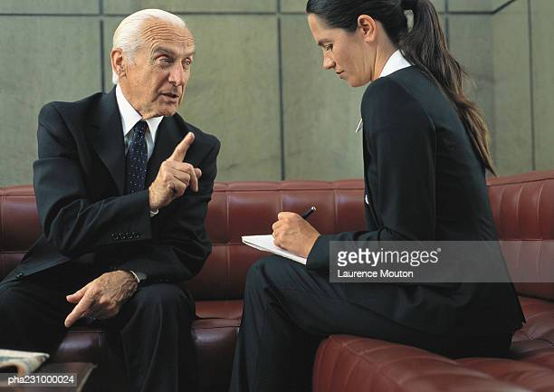 Senior businessman with businesswoman holding notepad, portrait
