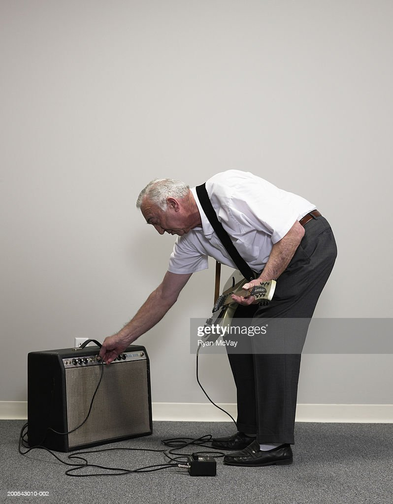 Senior businessman with electric guitar adjusting amplifier : Stock Photo