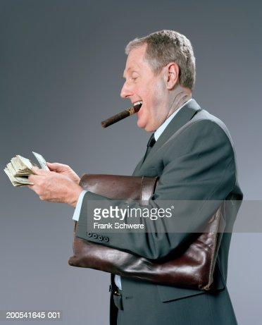 Senior businessman with shark gills counting money, side view : Stock Photo