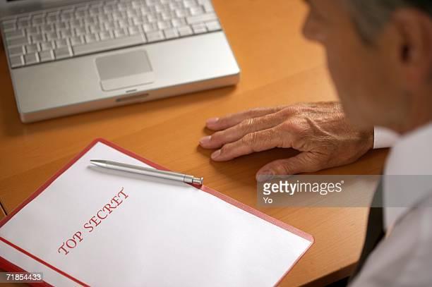 Senior businessman with Top Secret documents