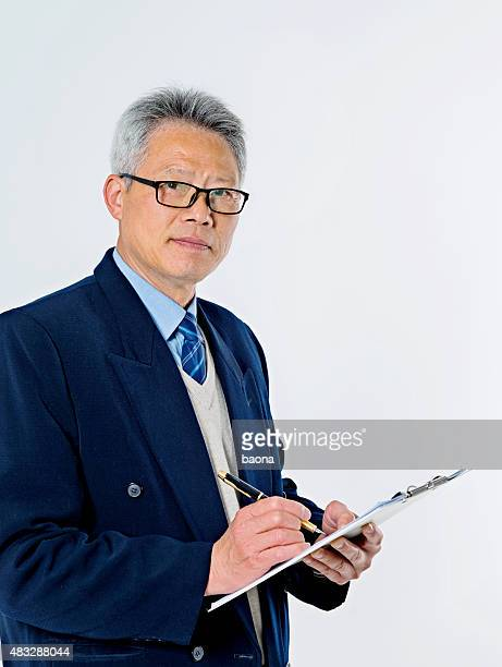 Senior businessman writing on a clipboard