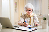 Senior businesswoman calculating taxes at home.