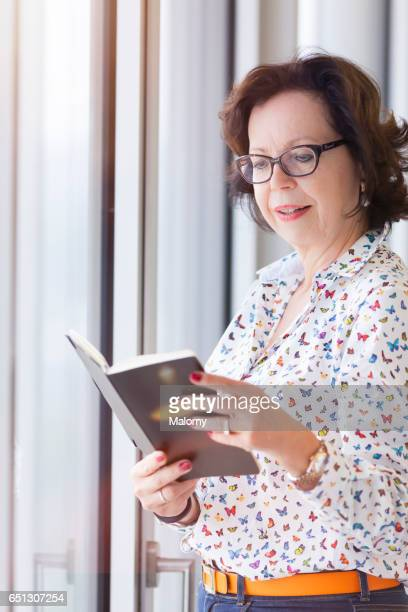 Senior businesswoman, female manager or CEO at the window in her office. Looking at her notebook, calendar. Seniorpreneurs