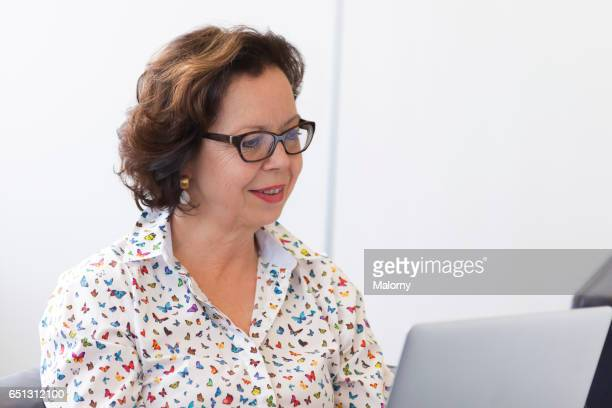 Senior businesswoman, female manager or CEO at the window in her office. Working on laptop computer. Seniorpreneurs