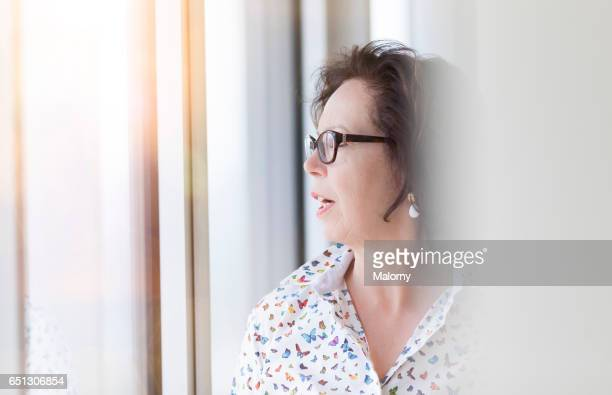Senior businesswoman, female manager or CEO at the window in her office. Seniorpreneurs