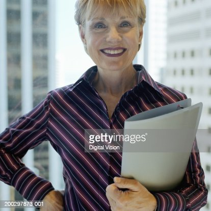 Senior businesswoman holding folder, smiling, portrait : Foto de stock