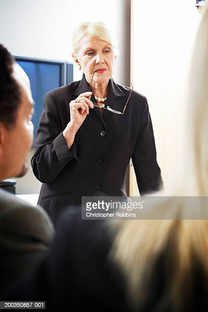 Senior businesswoman leading meeting, holding reading glasses to mouth