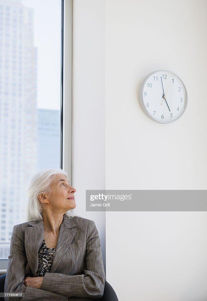 Senior businesswoman looking at clock