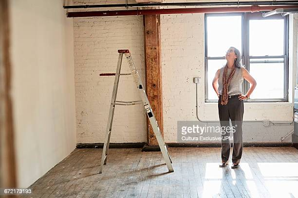 Senior businesswoman looking up in empty new office
