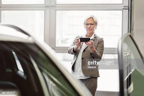Senior businesswoman photographing car through smart phone in dealership store