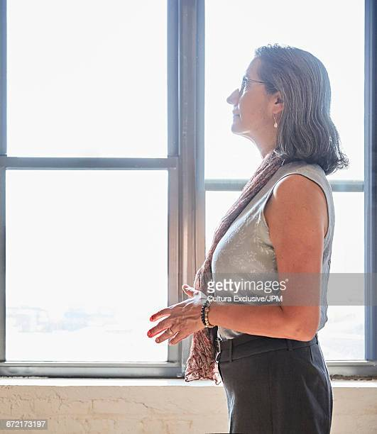 Senior businesswoman standing in front of new office window