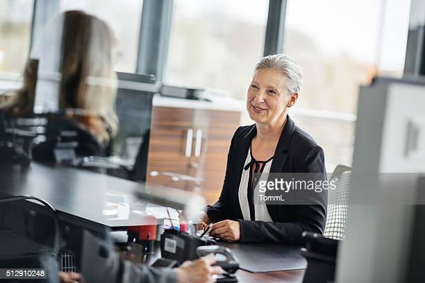 Senior Geschäftsfrau Gespräch mit Mitarbeiter