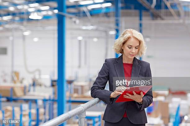 Senior businesswoman with clipboard in warehouse