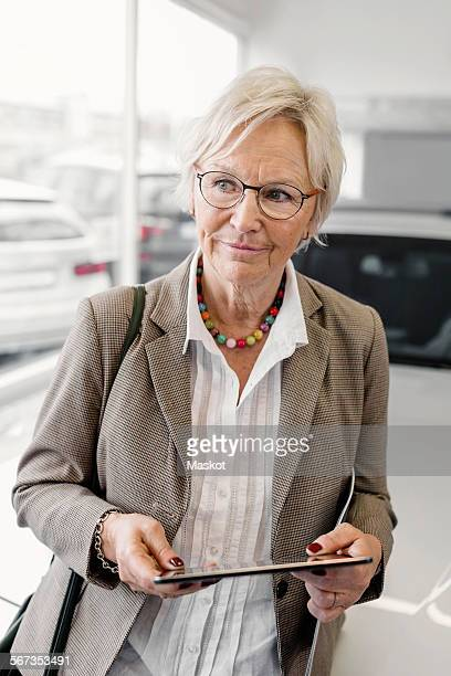 Senior businesswoman with digital tablet standing in car dealership store