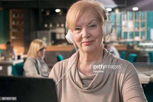 Senior Geschäftsfrau, die Arbeit am Laptop mit Hedphones auf Kopf im restaurant