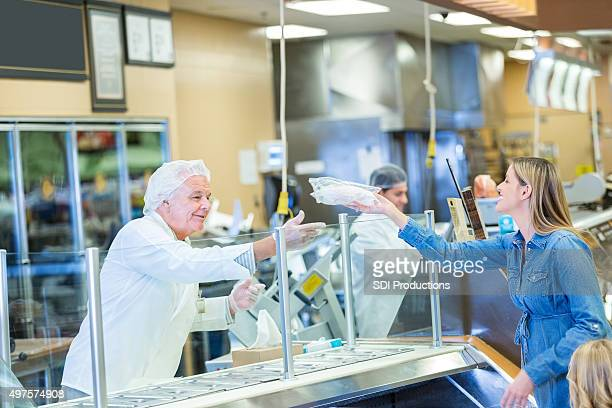 Senior butcher or employee helping customer in grocery store