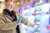 senior  buying cosmetics, for oral hygiene   in the supermarket
