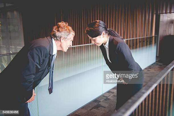 Senior Caucasian Businessman and Young Japanese Entrepreneur Bowing, Kyoto, Japan