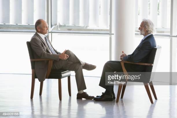 Senior Caucasian businessmen talking in office