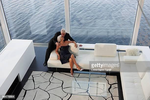 Senior Caucasian couple in evening wear in living room