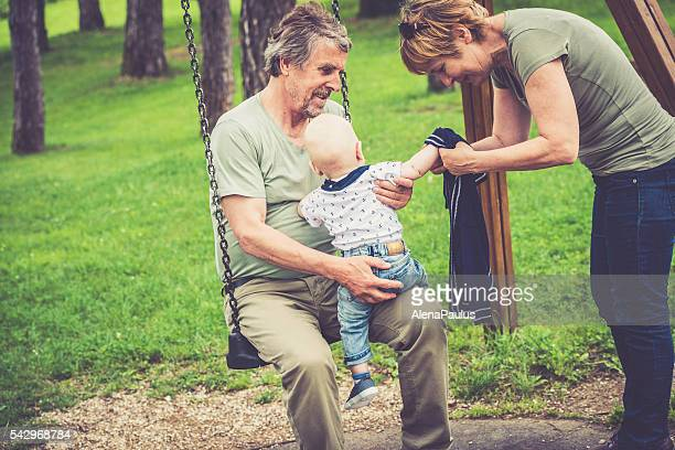 Senior caucasian couple outdoors dressing their grandson in city park