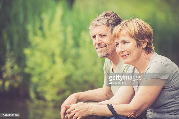 Senior caucasian couple outdoors portrait - looking around