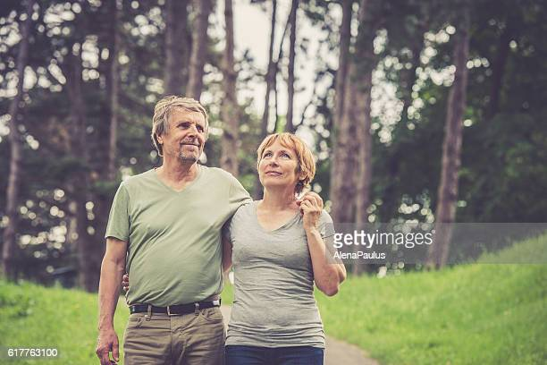 Senior caucasian couple walking, holding hands and hugging outdoors