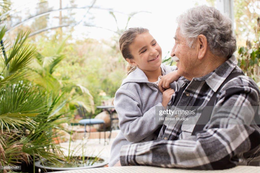 Senior Caucasian man and granddaughter smiling outdoors