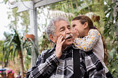 Senior Caucasian man and granddaughter whispering outdoors