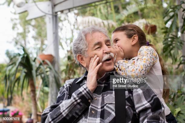 Senior Caucasian man and granddaughter whispering outdoors