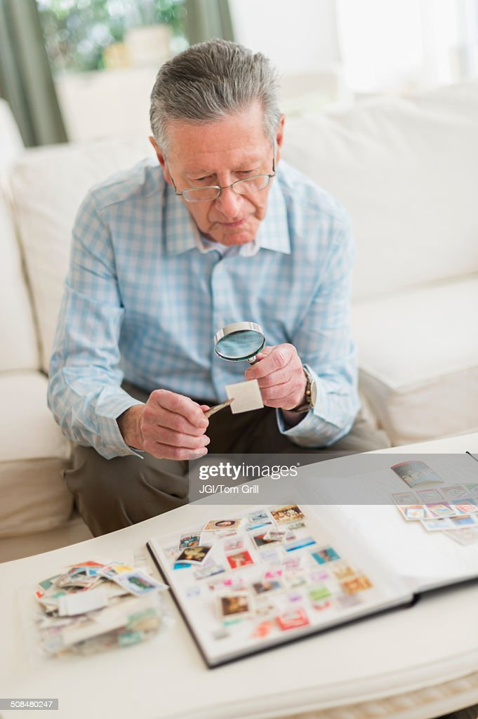 Senior Caucasian man examining stamp collection