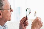 Senior Caucasian man examining stamp with magnifying glass