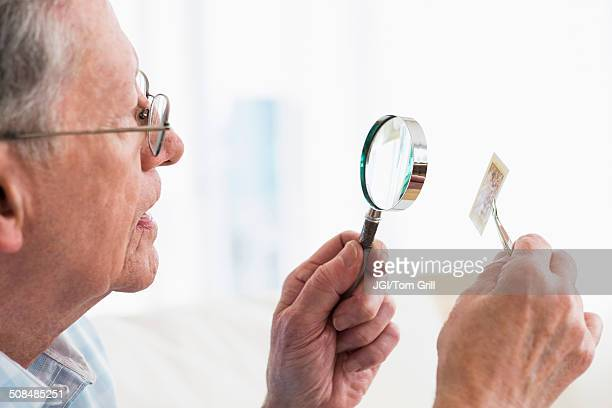 Senior Caucasian man examining stamp with magnifying glass