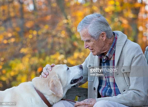 Senior Caucasian man petting dog on park bench