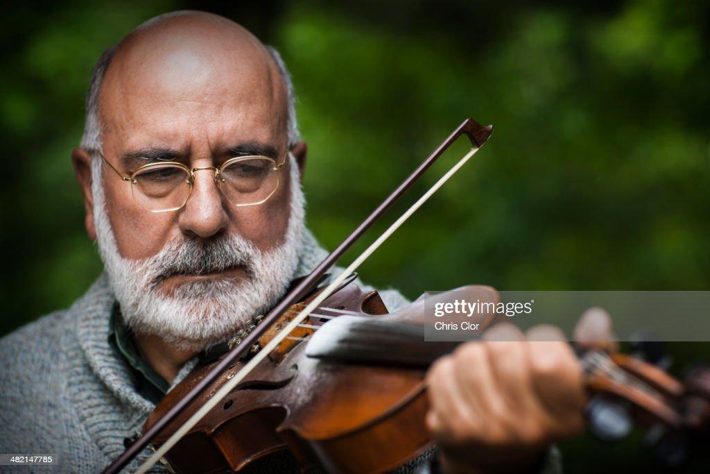 Senior Caucasian man playing violin outdoors