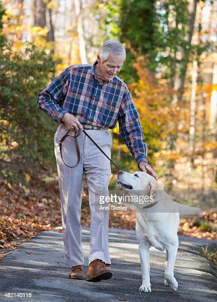 Senior Caucasian man walking dog in park