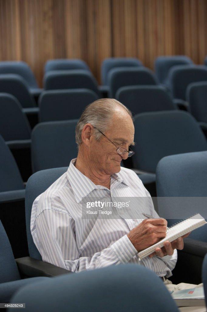 Senior Caucasian student taking notes in classroom