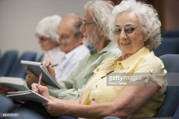 Senior Caucasian students taking notes in classroom