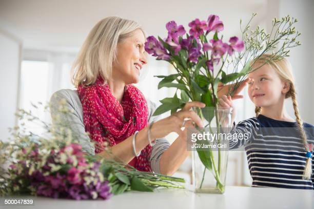 Senior Caucasian woman and granddaughter arranging flowers