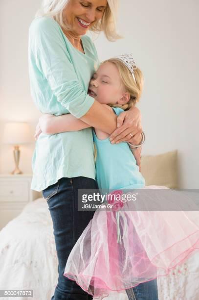 Senior Caucasian woman and granddaughter hugging