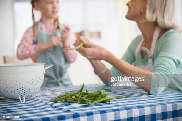 Senior Caucasian woman and granddaughter shucking peas together