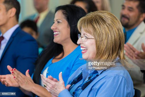 Senior Caucasian woman applauds during town hall meeting