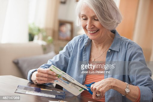 Senior Caucasian woman clipping coupons