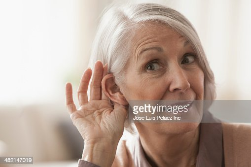 Senior Caucasian woman cupping her ear to listen