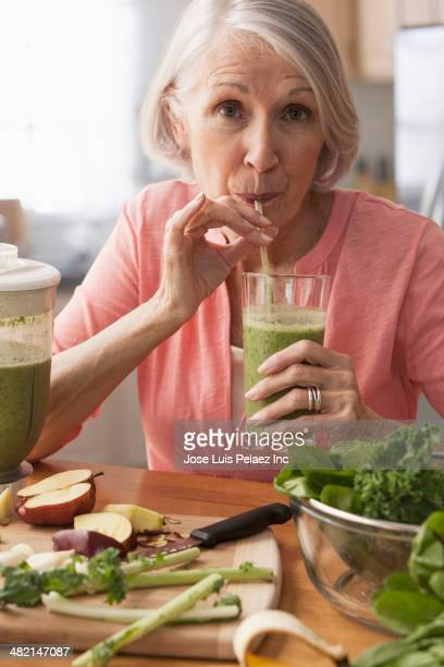 Senior Caucasian woman drinking green smoothie