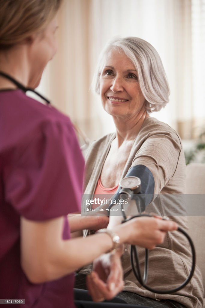 Senior Caucasian woman having blood pressure checked by nurse : Stock Photo