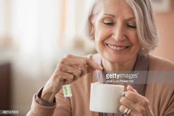 Senior Caucasian woman having cup of tea